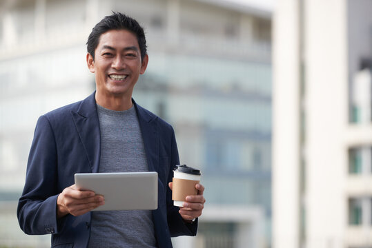 Portrait of happy middle-aged entrepreneur with digital tablet holding cup of take out coffee when standing outdoors