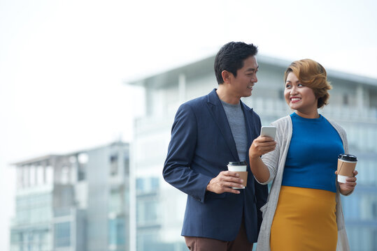 Cheerful mature business colleagues discussing funny meme about office workers on social media when drinking coffee outdoors during break