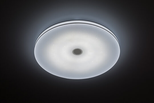 Ceiling round LED illuminator on a dark background. Modern lighting fixtures for the room.