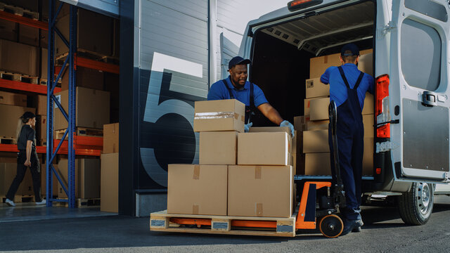 Outside of Logistics Warehouse with Open Door, Delivery Van Loaded with Cardboard Boxes. Truck Delivering Online Orders, Purchases, E-Commerce Goods, Wholesale Merchandise.