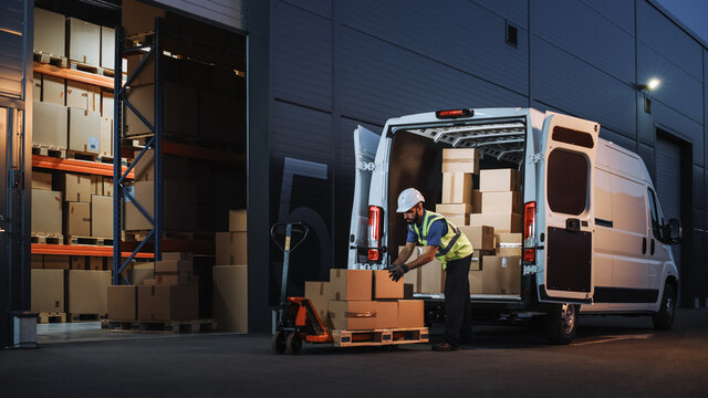 Outside of Logistics Distributions Warehouse Delivery Van: Worker Unloading Cardboard Boxes on Hand Truck, Online Orders, Purchases, E-Commerce Goods, Food, Medical Supply. Evening Shot
