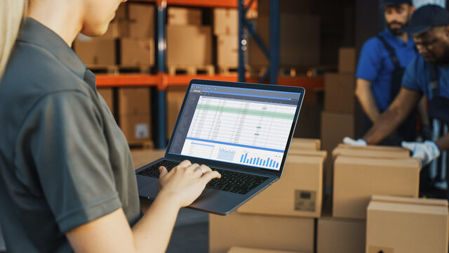 Female Manager Using Laptop Computer To Check Inventory. In the Background Warehouse Retail Center with Cardboard boxes, e-Commerce Online Orders, Food, Medicine, Products Supply. Over the Shoulder