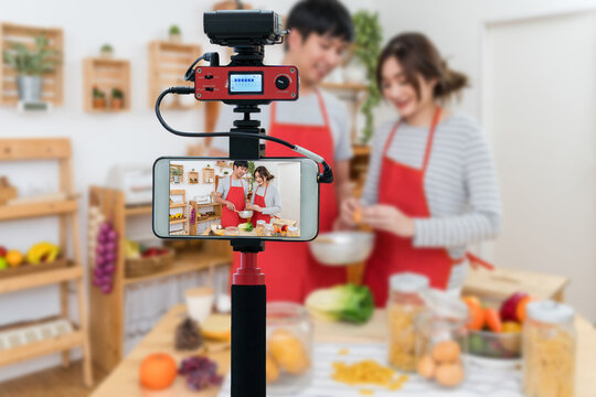 Closeup smart mobile phone taking Live of Happy Asian Lover or couple cooking in the kitchen room, Camera for photographer or Video and Live Streaming concept