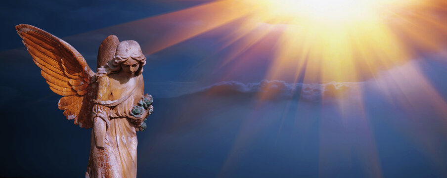 Antique statue of beautiful  angel in the sunlight against mountains in fog