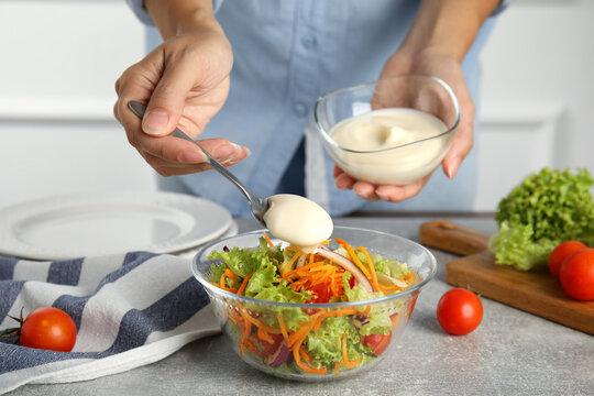 Woman adding mayonnaise to delicious salad at grey table, closeup