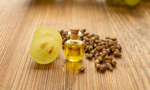 Grape Oil Seed in Small Vintage Bottle on Wooden Rustic Background