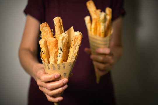 Cheese Straws and Sesame Seeds In A Paper Cone