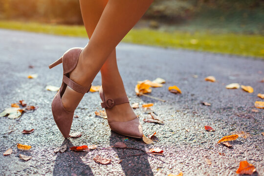 Close up of female shoes. Woman wears stylish brown high-heeled shoes in autumn park standing among falling leaves.