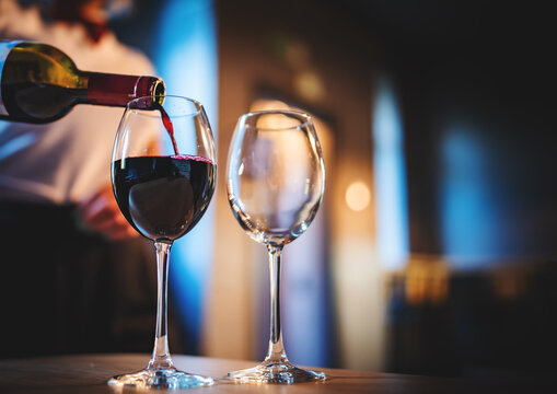 waiter pouring red wine into a glass in cafe or bar