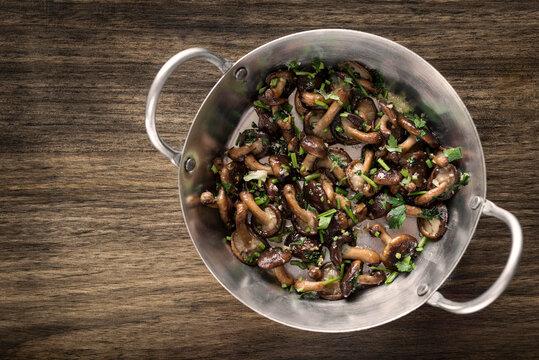 Shiitake mushrooms sauteed with garlic and herbs in metal pan