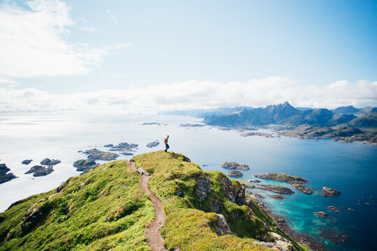 Beautiful sunny day, man on hike high up in mountains, overlooking blue ocean. Adventure seeker traveller on top of cliff