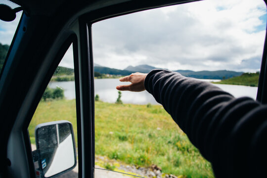 Travel lifestyle vibes, woman hold hand out of car window. Vanlife nomad trip. Woman catch wind with hand out of passenger window of camper van
