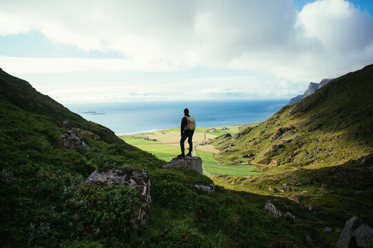 Man with hiking backpack stand on top of mountain, overlook epic views and nordic scandinavian landscape. Modern adventure traveller concept. Young people spend quality time in nature