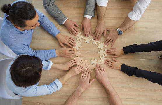 Diverse business people team group joining puzzle pieces sitting at office desk table view from top above. Collaboration and cooperation strategy, teamwork and teambuilding concept