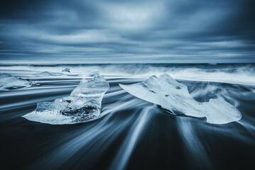 Fototapeta Majestic pieces of the iceberg sparkle on black sand. Location place Jokulsarlon lagoon, Iceland, Europe. obraz