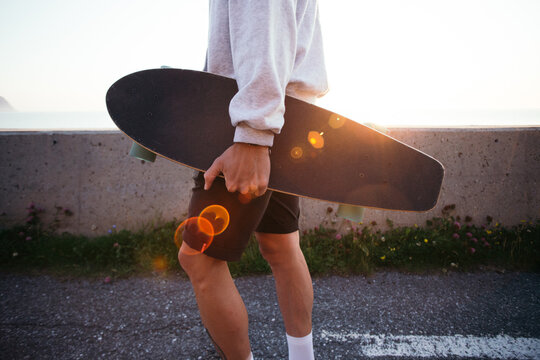 Side view of man carry longboard in his hand. Casual dressed young man in grey hoodie walk with skateboard in sunset light with leaks