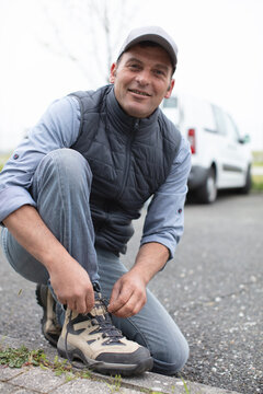 male builder ties his laces shoes