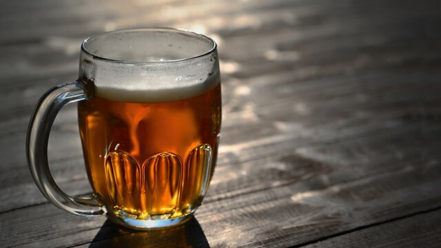 Refreshing fresh draft beer in a dewy glass. Good and honest Czech quality beer on a wooden table background.