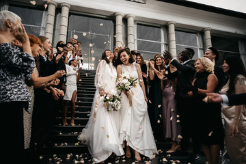 Candid shot of two female lesbian LGBT brides walking down the stairs during their wedding ceremony...