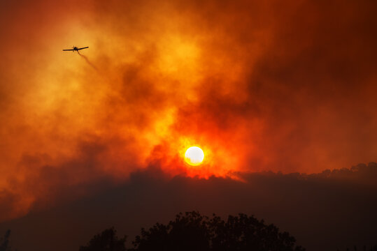 Plane leaving trail of chemicals to fight wildfire. Dramatic red smoke against setting sun
