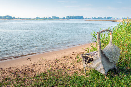 Broken rattan chair along the wide Dutch river Waal. The photo was taken near the village of Herwijnen in the province of Gelderland at the beginning of the morning at the end of the summer season.
