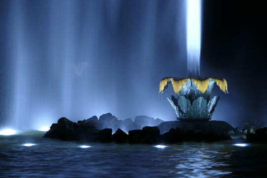 Illuminated water fountain at night in the Herrenhausen Gardens in Hanover Germany. In the background you can still see a small water fountain. Everything glows in blue and orange in the black night.