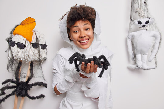 31st of October. Positive Afro American woman holds spider makes magic trick smiles happily develops imagination wrapped in white fabric poses indoor. Fantasy and creativity. Its too cute to spook