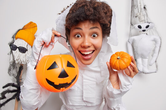 Positive female halloween character holds traditional pumpkins poses against October decorations carved jack o lantern prepares for party poses against white background creats spooky holiday