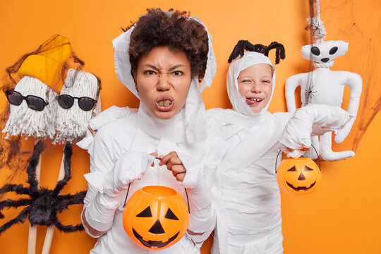 Afro American woman and her daughter prepare for Halloween party hold holiday attributes wear white zombie costumes isolated over orange studio background. People mystery and celebration concept