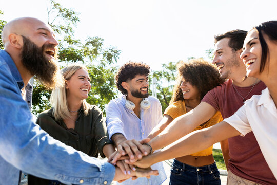 Group of united multiracial people stacking hands together - Cooperation, collaboration, community and unity concept with multiethnic young college students celebrating together on campus university
