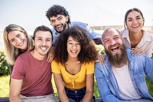 Multiracial group of young people - Happy millennial friends from different cultures smiling at smartphone camera - Friendship and youth concept with diverse millennial students sitting together