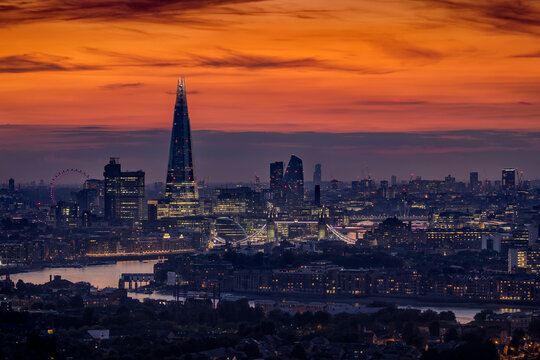 The illuminated skyline of London, United Kingdom, just after sunset with Thames River, Tower Bridge and modern office skyscrapers in the City