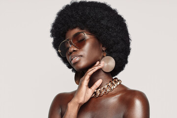 Obraz Portrait of beautiful young African woman in golden jewelry keeping eyes closed and touching face - fototapety do salonu