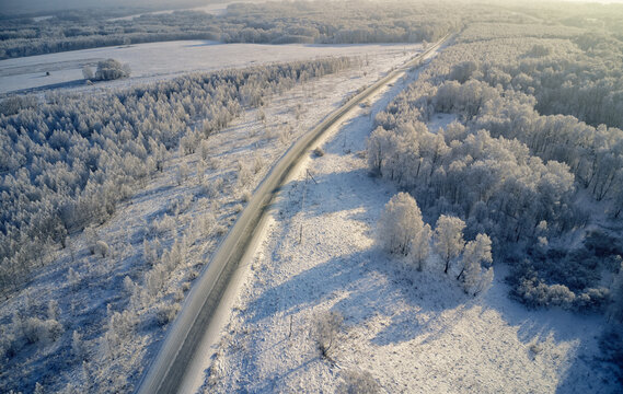 Aerial photo of winter road surrounded by birch forest. Drone shot of trees covered with hoarfrost and snow.
