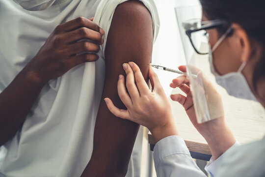 Young man visits skillful doctor at hospital for vaccination . Covid 19 and coronavirus vaccination center service concept .