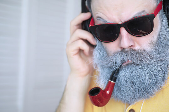 Guy smoking tobacco pipe. Hipster with grey beard and mustache. Bad habits conce