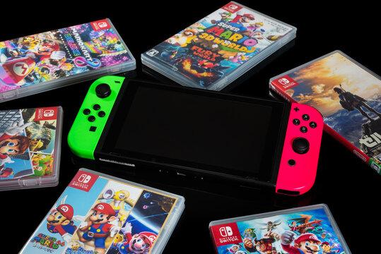 Fukuoka, Japan - september 19, 2021 : nintendo switch with various game cartridges isolated on black background