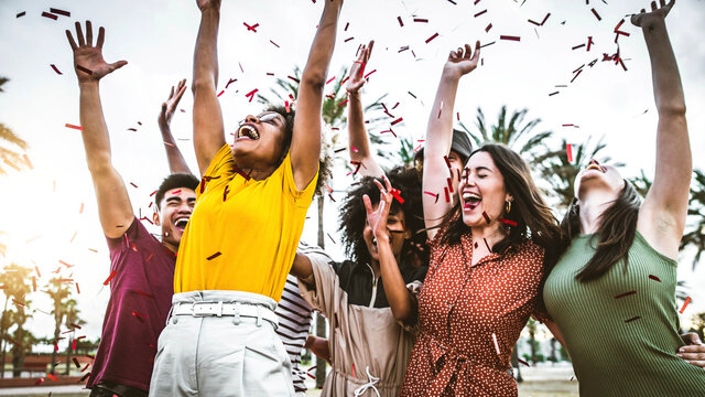 Group of friends enjoying party throwing confetti in the air - Multicultural young students having fun celebrating and laughing out loud outdoor - Youth, friendship and summertime concept.