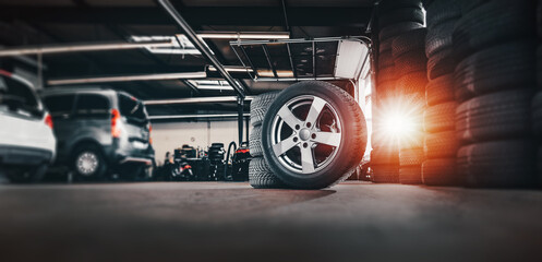 tire at repairing service garage background. Technician man replacing winter and summer tyre for...