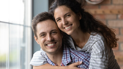 Head shot portrait of smiling beautiful loving sincere family couple posing together in own house....