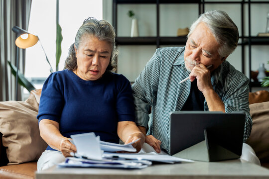Serious stressed asian senior old couple worried about bills discuss unpaid bank debt paper, sad poor retired family looking at tablet counting loan payment worry about money problem