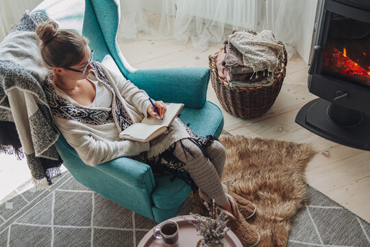 Young woman write in notebook sitting in armchair by fireplace