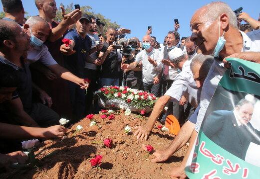 People put roses at the burial site of former Algerian President Abdelaziz Bouteflika at El Alia cemetery, in Algiers