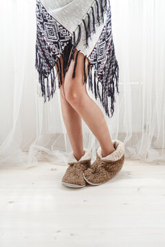 Female legs in warm cozy slippers at home