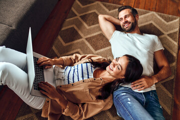 Obraz Young dreaming couple lie on the floor on the carpet at home. A married couple is relaxing in the living room. A woman with a laptop lies on a man on the floor. Work from home. Online shopping. - fototapety do salonu