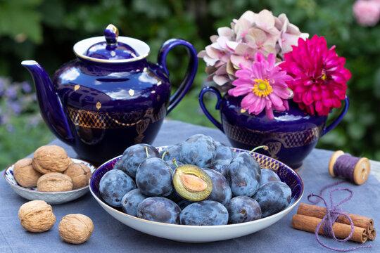 Tischdekoration mit frischen Zwetschgen, Porzellan und Blumenstrauß