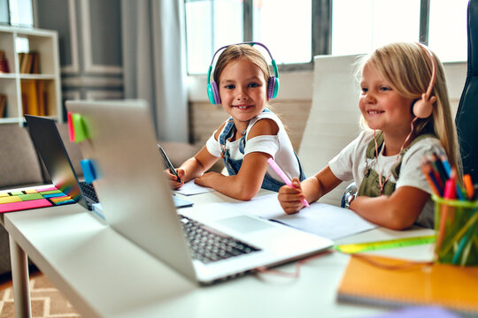 Online training. Two schoolgirl sisters in headphones listen to lessons on laptops. School at home in a pandemic and quarantine.