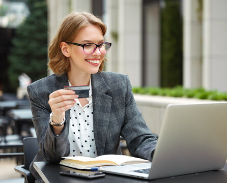 Cheerful business lady with credit bank card paying online while sitting at cafe table with laptop