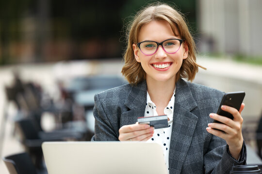 Positive business lady with mobile phone and credit bank card smiling at camera working remotely outdoors