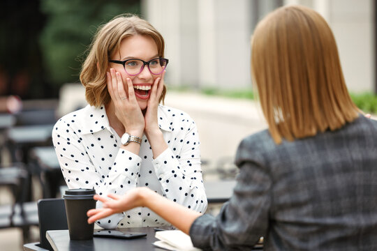 Excited surprised businesswoman hearing good amazing news from business partner at outdoor cafe